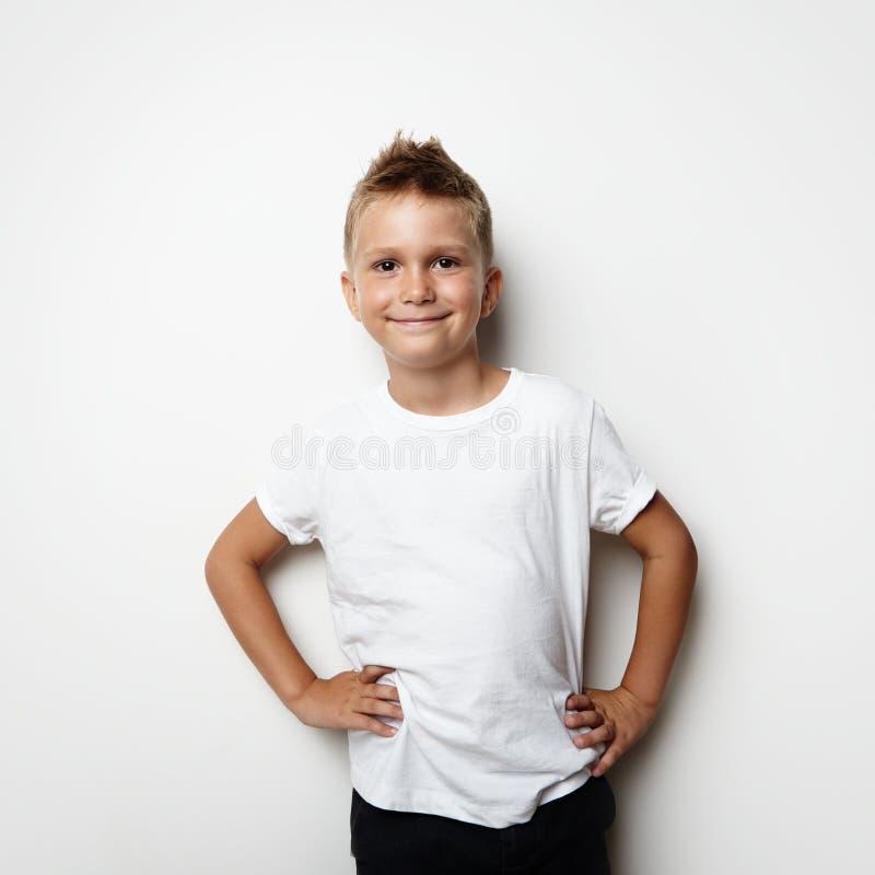T-shirt blanc de port de sourire et shorts de garçon sur photos libres de droits