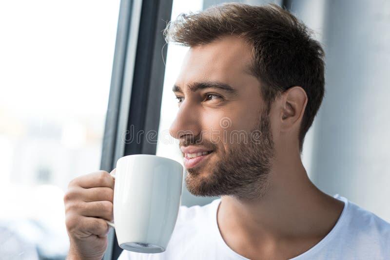 T-shirt branco vestindo de sorriso do homem novo que está pela janela com copo fotos de stock royalty free