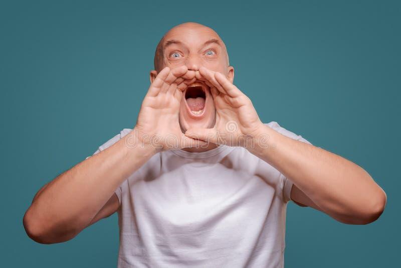 T-shirt branco vestindo do homem feliz considerável, indivíduo que fala alto, isolado no fundo azul foto de stock