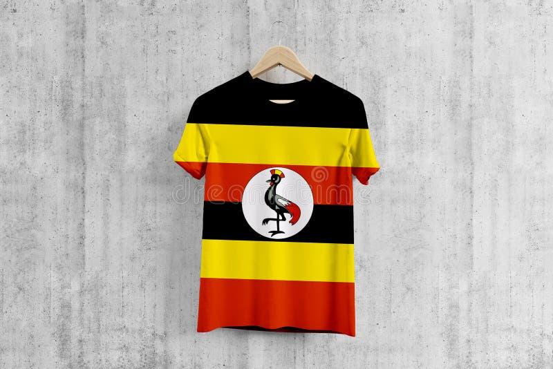 T-shirt da bandeira de Uganda no gancho, ideia uniforme do projeto da equipe Ugandan para a produção do vestuário Desgaste nacion ilustração stock