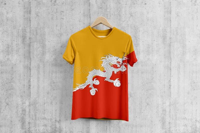 T-shirt de drapeau du Bhutan sur le cintre, idée uniforme de conception d'équipe bhoutanaise pour la production de vêtement Usage illustration stock