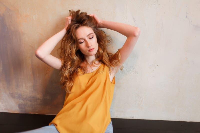T-shirt de port de fille tendre, jeans posant contre le mur rugueux de grenier, style urbain minimaliste photographie stock