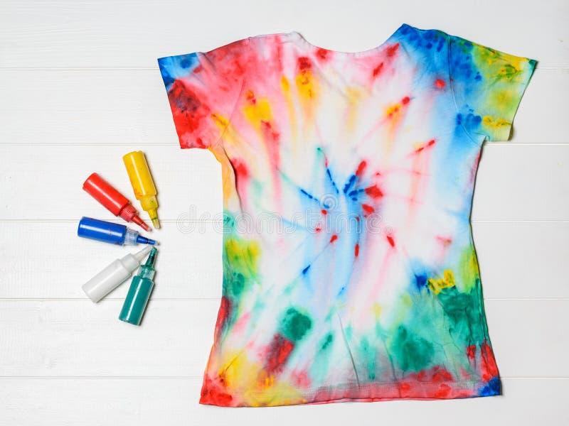 T-shirt in de stijl van de bandkleurstof met kleuren op een witte houten lijst wordt geschilderd die Vlak leg stock foto's