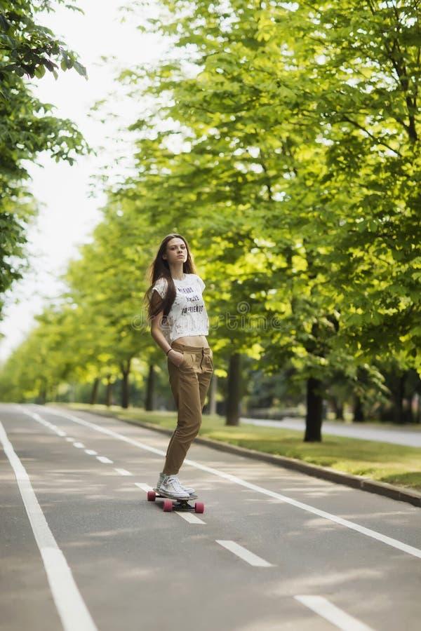 T-shirt do moderno da moça, short e passeios bonitos das sapatilhas na trilha no parque em um longboard skateboarding lifestyle fotos de stock royalty free