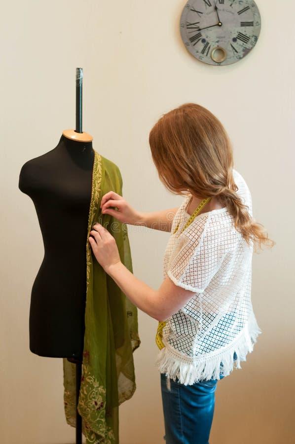 T-shirt et jeans tenant et modelant des vêtements avec le tissu vert sur le mannequin noir photographie stock