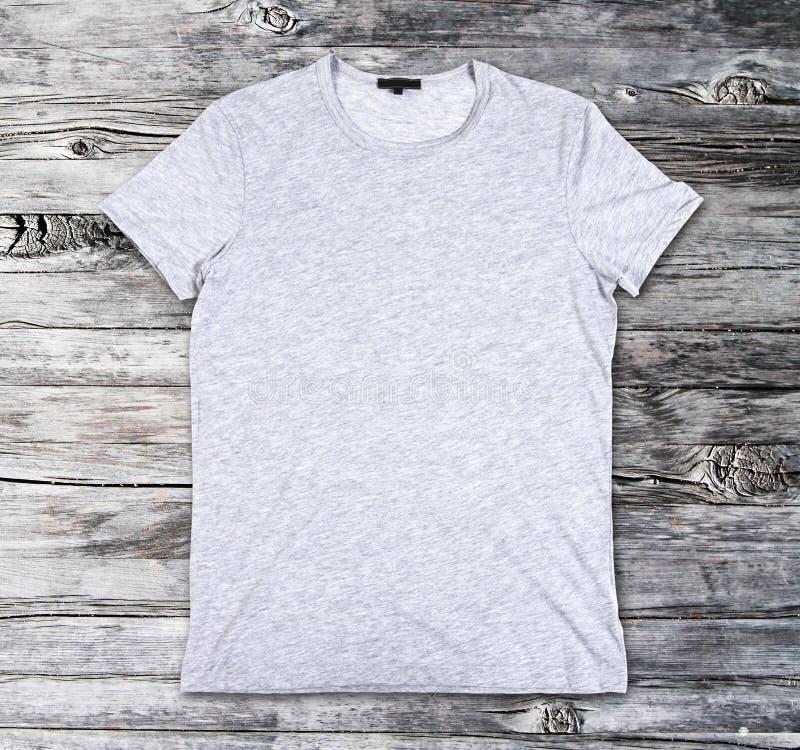 T-shirt gris vide sur une surface en bois images stock