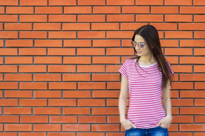 T-shirt listrado vestindo da mulher atrativa e óculos de sol elegantes que levantam contra a parede de tijolo vermelho, estilo da fotografia de stock royalty free
