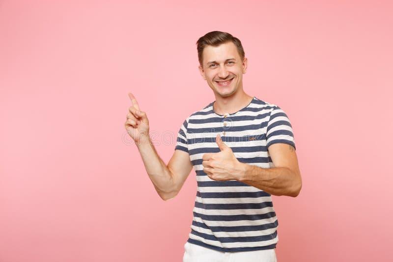 T-shirt listrado vestindo de sorriso entusiasmado do homem novo do retrato que aponta o indicador de lado no espaço da cópia isol imagens de stock
