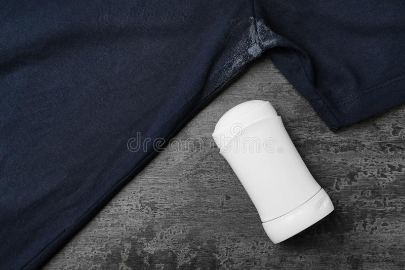T-Shirt mit Fleck des desodorierenden Mittels auf grauem Hintergrund lizenzfreies stockbild