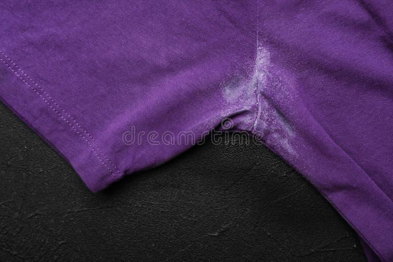T-Shirt mit Fleck des desodorierenden Mittels auf schwarzem Hintergrund stockbilder