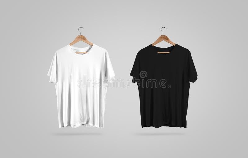 T-shirt noir et blanc vide sur le cintre, maquette de conception photos libres de droits