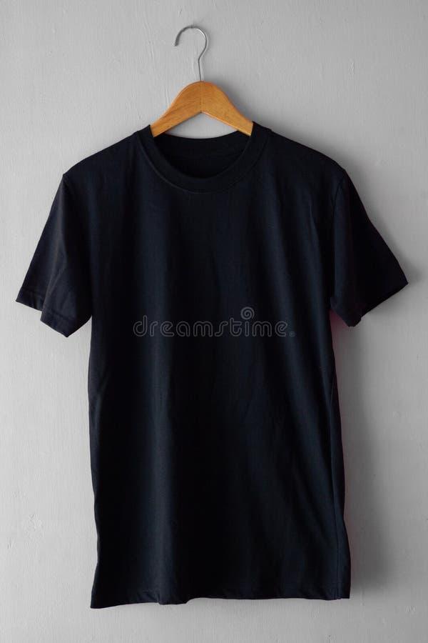 T-shirt noir sur la couleur en bois de noir de cintre pour la moquerie  images stock