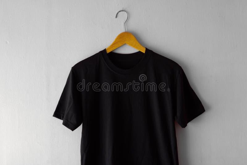 T-shirt noir sur la couleur en bois de noir de cintre pour la moquerie  photo stock