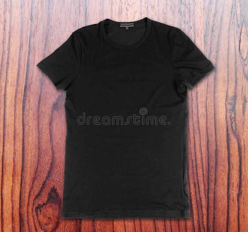 T-shirt noir vide sur le fond en bois images stock