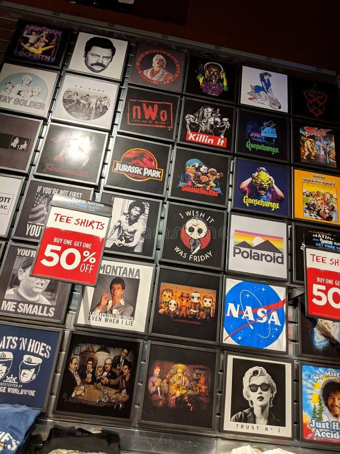T-shirt que caracterizam Goosebumps, Jurassic Park, NASA, agora, Ric Flair, amigos, Mario Kart super para a venda em Spencer fotografia de stock royalty free