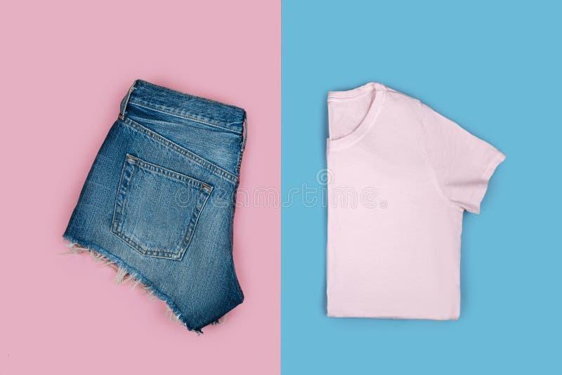 T-shirt rose et shorts bleus d'isolement sur le fond coloré photographie stock