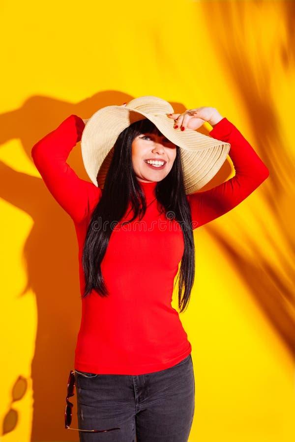 T-shirt rouge d'ombre de lunettes de soleil du soleil de chapeau de paille de fille de fond jaune-orange tropical clair de jeune  photo stock
