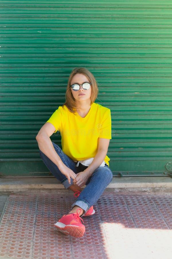 T-shirt vestindo, cal?as de ganga e ?culos de sol da mulher bonita sentando-se na ?rea pedestre perto da constru??o da cidade imagens de stock