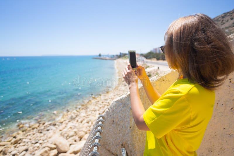 T-shirt vestindo, cal?as de ganga e ?culos de sol da mulher bonita Usa seu telefone celular que fica perto do litoral do mar imagens de stock