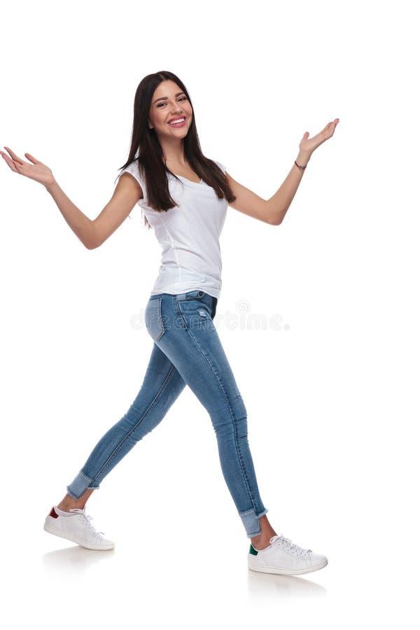 T-shirt vestindo da mulher alegre que anda para tomar partido ao levantar as mãos imagem de stock royalty free