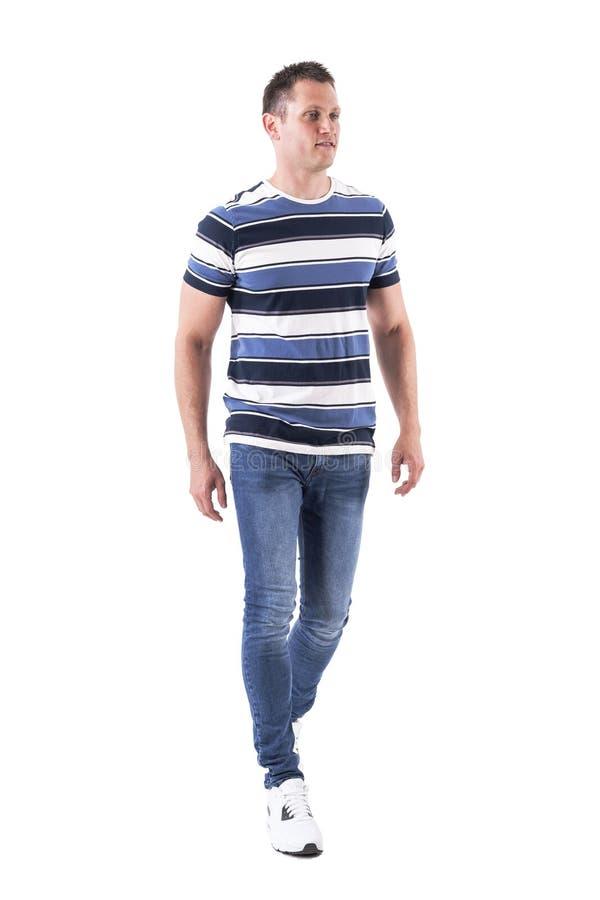 T-shirt vestindo e calças de brim do homem ocasional relaxado fresco que andam ocasionalmente foto de stock royalty free