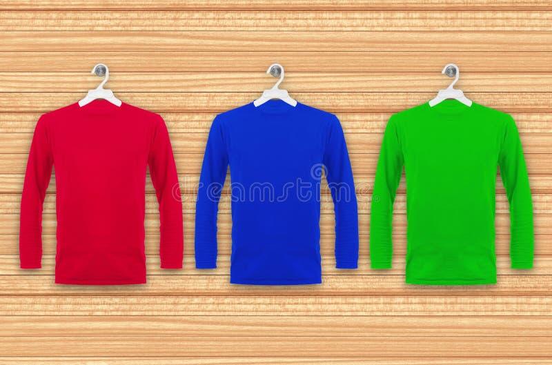 T-shirts coloré avec de longues douilles accrochant sur un mur en bois images stock