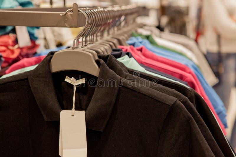 T-shirts coloré sur des cintres Vêtements élégants du ` s d'hommes Étalage, vente, faisant des emplettes Concept de mode et de co photos libres de droits