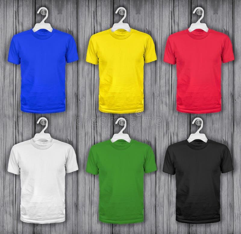 T-shirts colorés accrochant sur un mur en bois photo stock