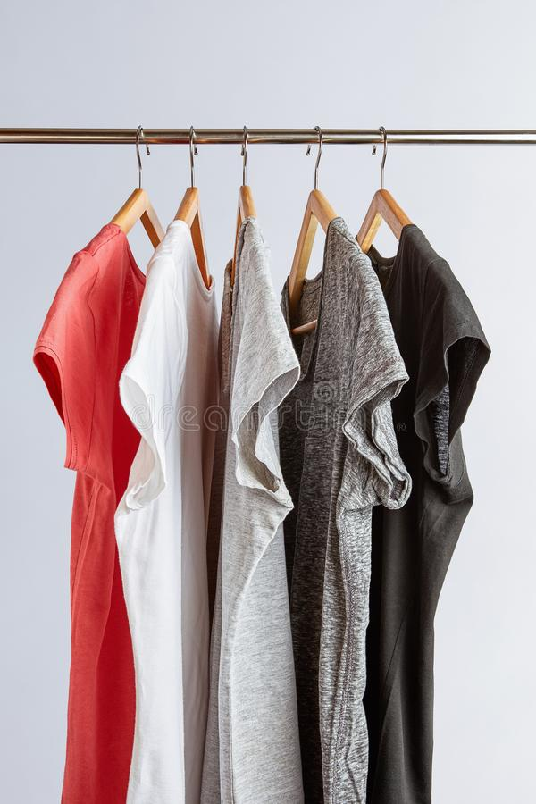 T-Shirts in neutral colors on rack. Capsule wardrobe concept. T-Shirts in neutral colors hanging on a clothing rack. Minimalist wardrobe stock image