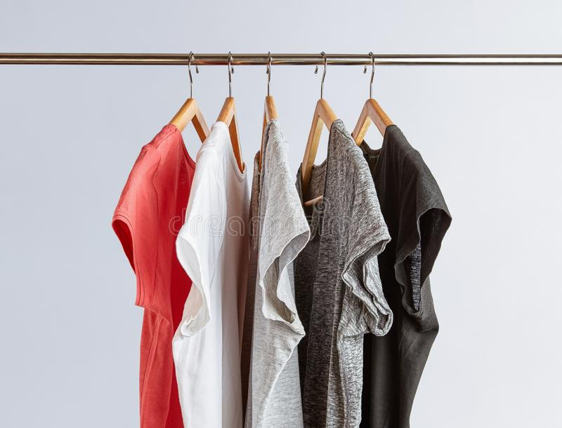 T-Shirts in neutral colors on rack. Capsule wardrobe concept. T-Shirts in neutral colors hanging on a clothing rack. Minimalist wardrobe royalty free stock photos