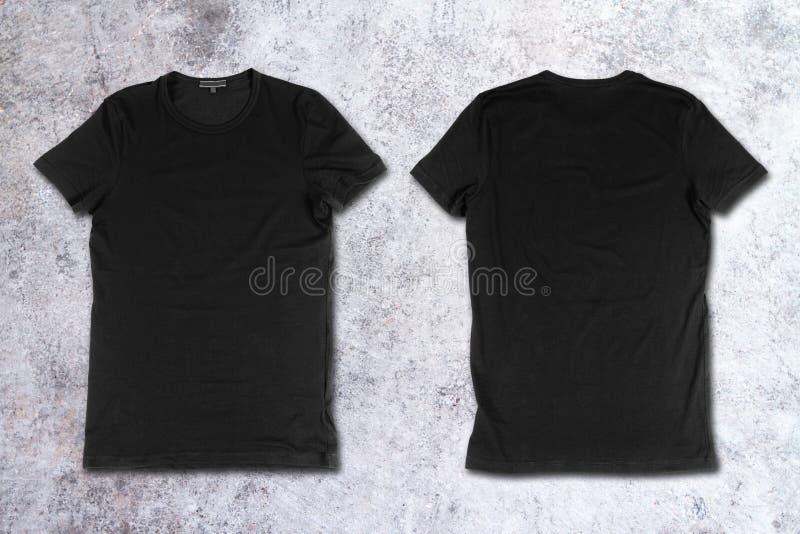 T-shirts noirs vides sur une surface en béton image stock