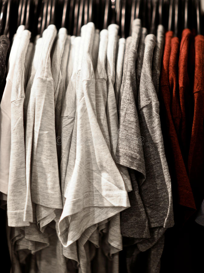 T-shirts on plastic hangers royalty free stock photo