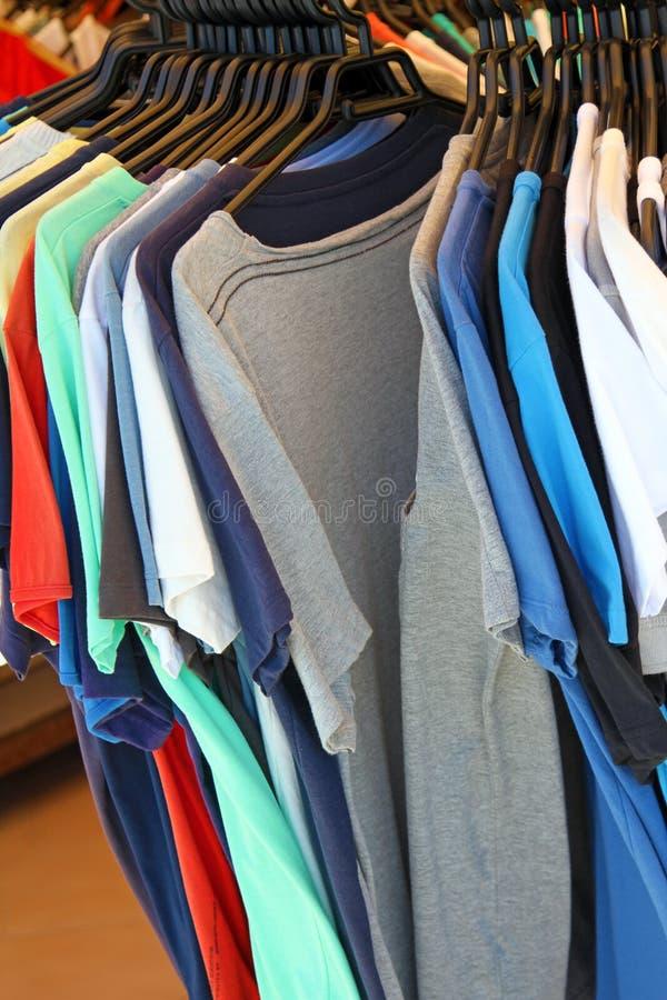 T-shirts sur le cintre dans la boutique de vêtements photo stock