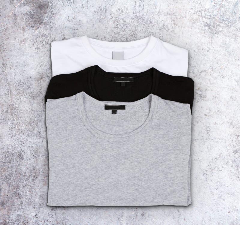 T-shirts vides sur une surface en béton photographie stock libre de droits