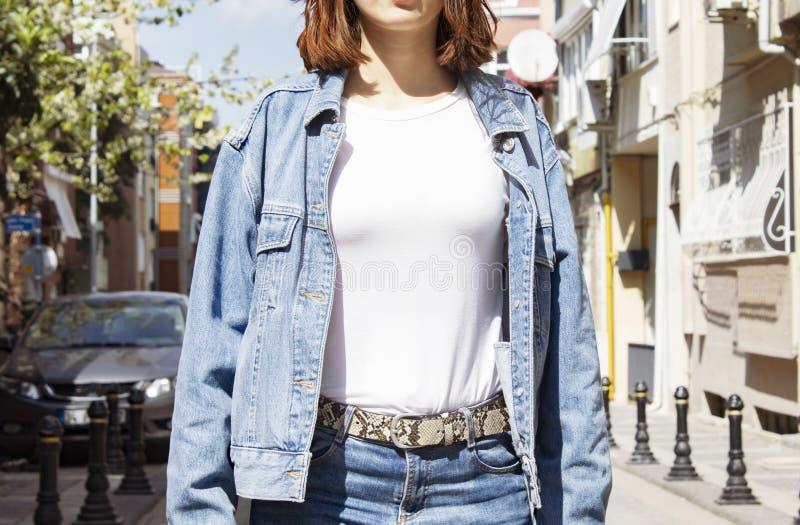 T-skjorta och grov bomullstvill för mall- och modellmellanrum som vit poserar mot den gråa gataväggen, för trycklager arkivbild
