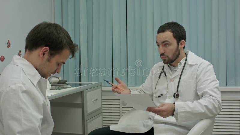 ` T som för mentordoktor isn är lycklig med resultat av medicinsk övning av allmäntjänstgörande läkaren arkivbild