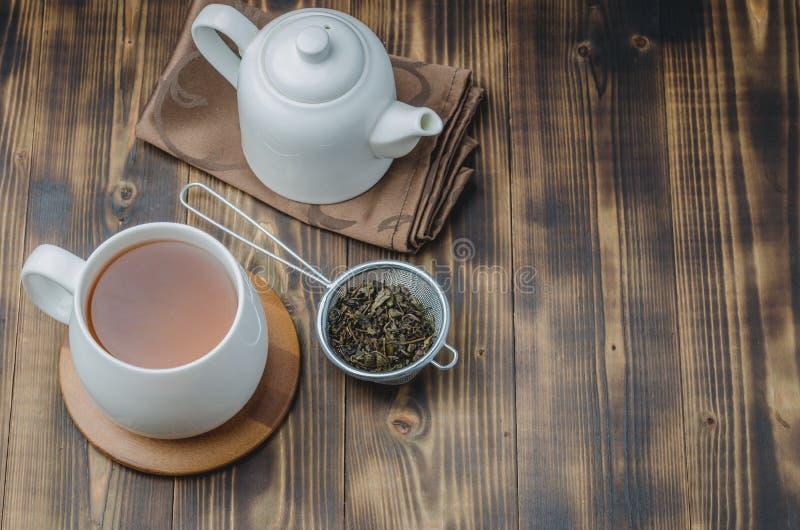 T? Tazza bianca di tè, di tè asciutti e della tavola di legno di ona della teiera Vista superiore, Copyspace immagine stock libera da diritti