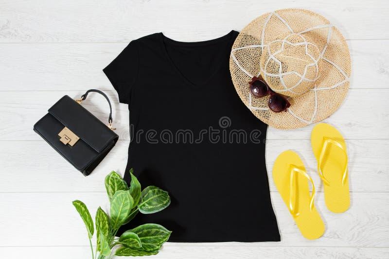 T-tröja, svart och tofflor T-shirt Mockup platt med sommartillbehör Hatt, väska, gula flip-flockar och solglasögon på trä royaltyfria bilder