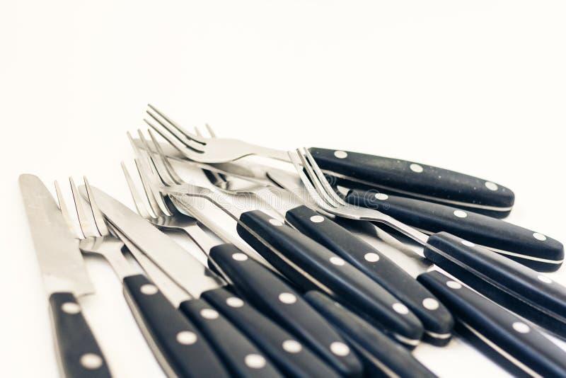 T?tt upp sex knivar och gafflar som isoleras p? vit bakgrund royaltyfri foto