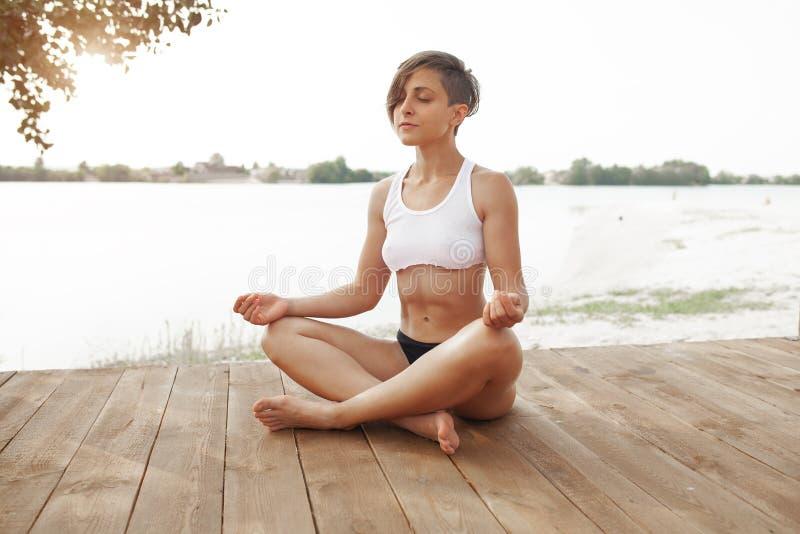 ?t? Une belle fille avec une coupe de cheveux courte pratique le yoga en position de lotus Femme sportive m?ditant par le lac photographie stock libre de droits