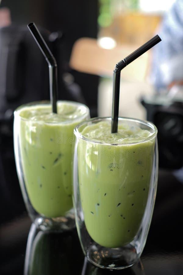 T? verde ghiacciato in vetro con ghiaccio sulla tavola in caffetteria fotografia stock libera da diritti