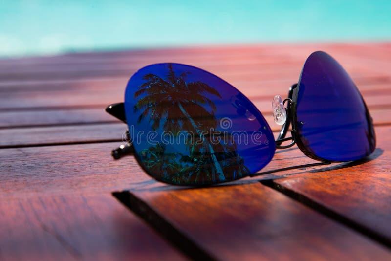 ?t? Verres de style avec la réflexion de paume qui a placé sur une table en bois sur la côte de la mer des Caraïbes photo libre de droits