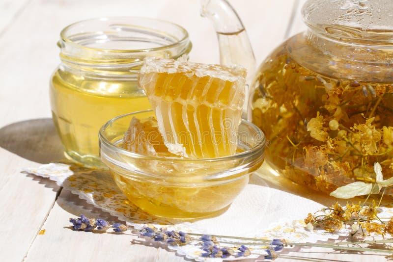 T? y flores de la lavanda del tilo de la tetera en la tabla de madera blanca con el peine de la miel y el tarro frescos de miel f fotografía de archivo