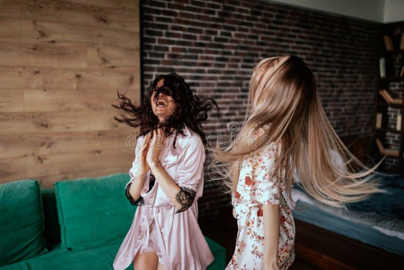 Tańczenie pięknych pań w piżamie rano, cieszenie się chwilą w wielkim studio mieszkania z obrazy stock