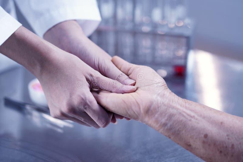Ta äldreomsorgfolk, doktor som tröstar patienten, så arkivbilder