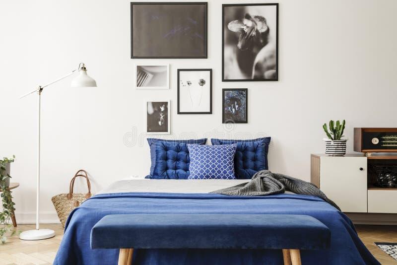 Ta av planen framme av säng med marinblåa kuddar mellan lampan och kabinettet i sovruminre Verkligt foto royaltyfria foton