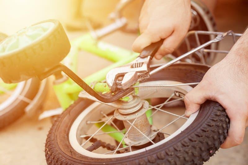Ta bort utbildningshjulen Fader som reparerar hans ungecykel fotografering för bildbyråer