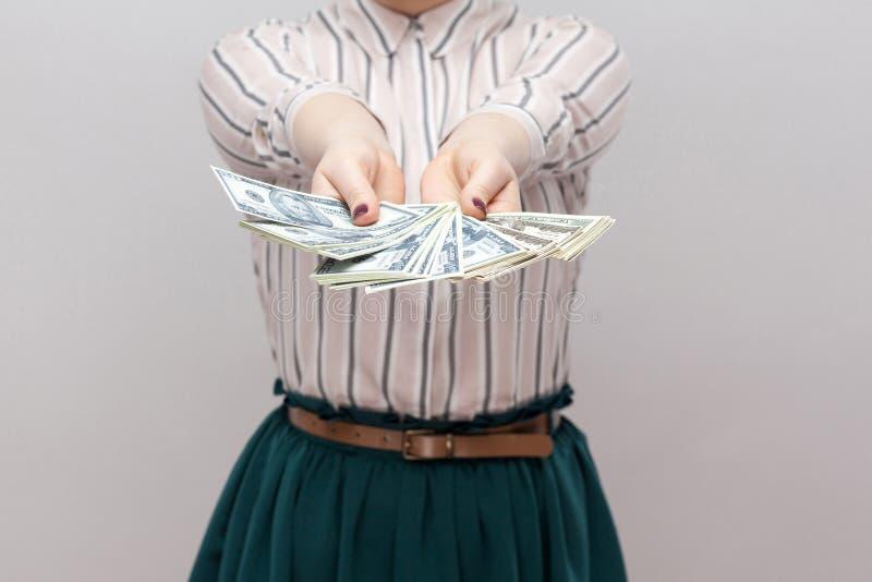 Ta det! Nära övre stående av den lyckade kvinnan i anseende för randig skjorta som rymmer många dollar, demonstrationsfan av peng arkivbild