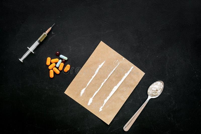 Ta droger, begrepp för drogböjelse Vitt pulver som hjältinnan eller kokain, drogspårpiller, sked, injektionsspruta på svart royaltyfri fotografi