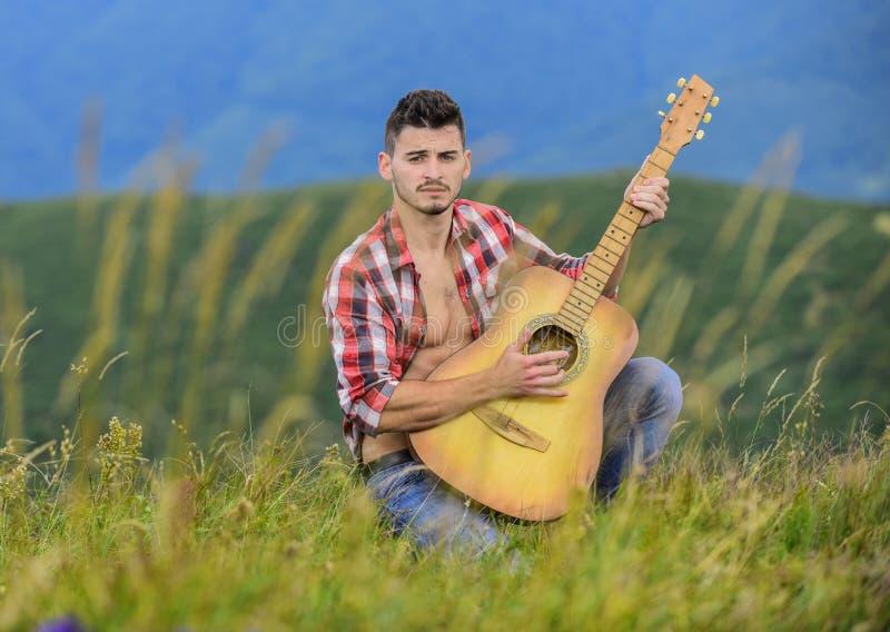 Ta med dig musik till livet sexig man med gitarr i schaktad tröja hipster mode camping och vandring i väst glad och royaltyfri fotografi